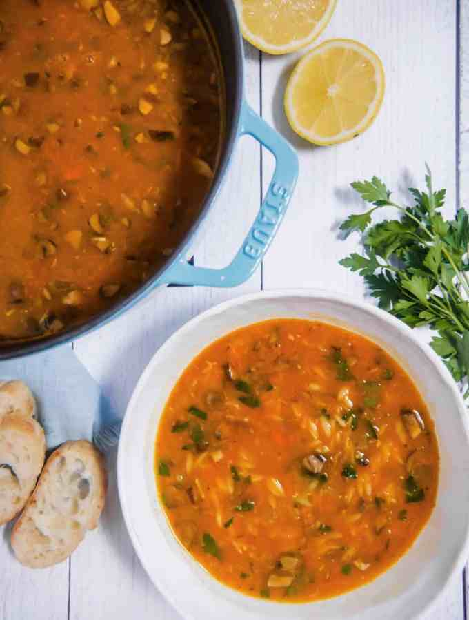 overhead photo of a dutch oven filled with vegetable orzo soup, a bowl of the soup, slices of bread, and lemons