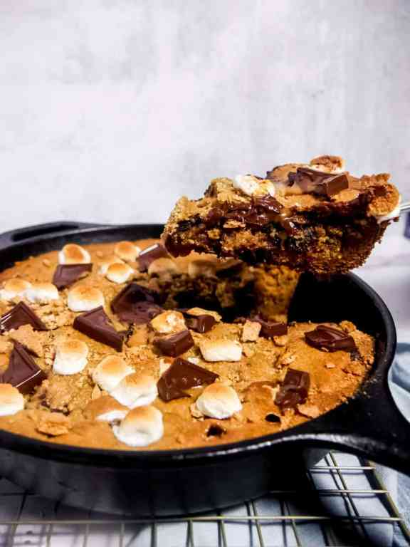 A slice of smores skillet cookie being lifted out of the cast iron skillet