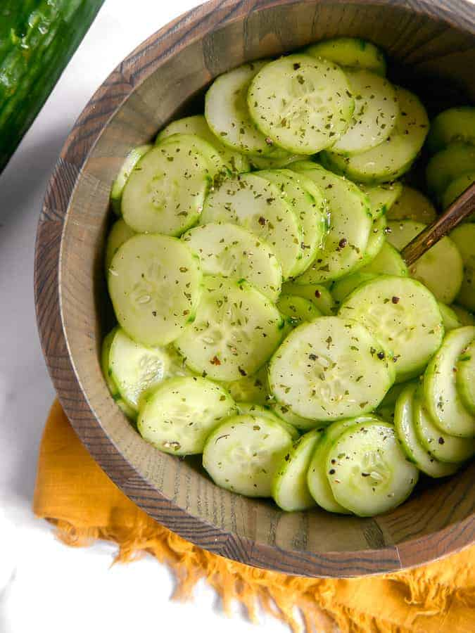 close up of cucumber salad in a wooden bowl
