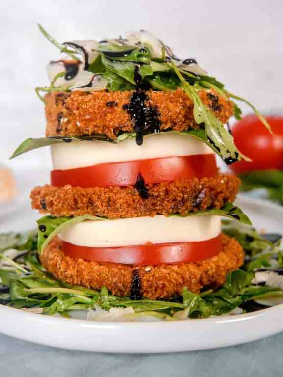close up of a stack of crispy eggplant, tomato, mozzarella, arugula salad, piled high on a white plate with a red tomato, basil, and parmesan with balsamic glaze dripping off