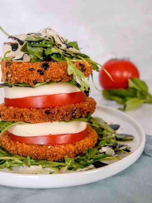 close up of a stack of crispy eggplant, tomato, mozzarella, arugula salad, piled high on a white plate with a red tomato, basil, and parmesan cheese block in the background
