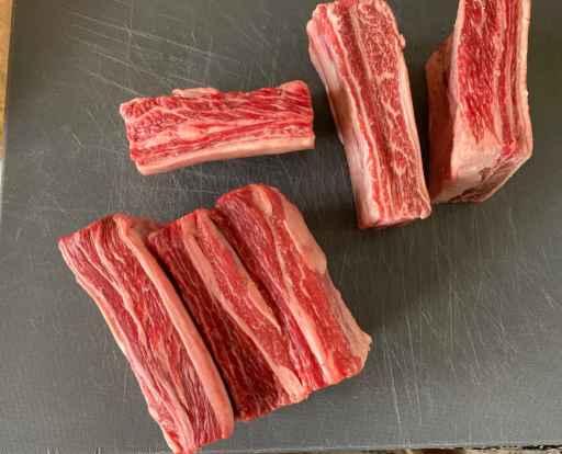 raw beef short ribs laying on a cutting board