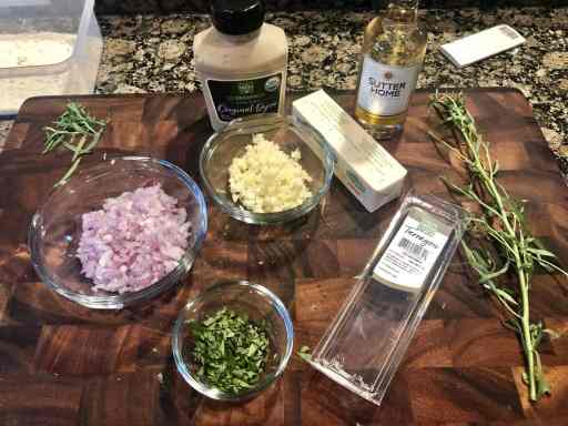 photo of a cutting board with minced shallot, minced garlic, fresh taragon in a bowl, dijon mustard, and a fresh tarragon plant