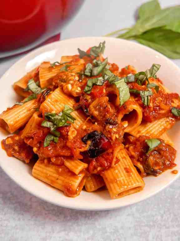 close up of white bowl of rigatoni pasta in eggplant red sauce topped with fresh basil