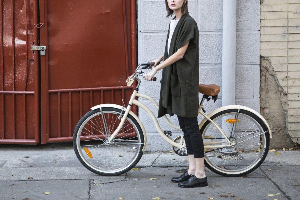 Donna elegante con una bici bianca