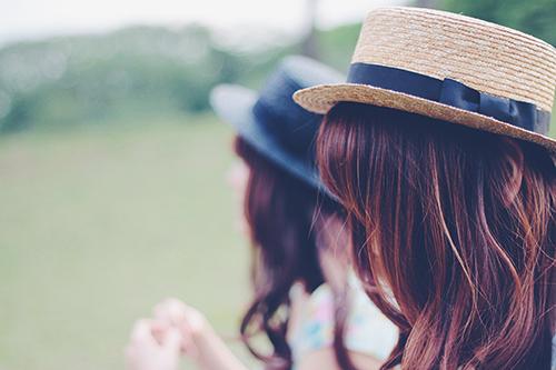 「友達」「双子ルック」「女性・女の子」「巻き髪」「帽子」「春」「芝生」「草原」などがテーマのフリー写真画像
