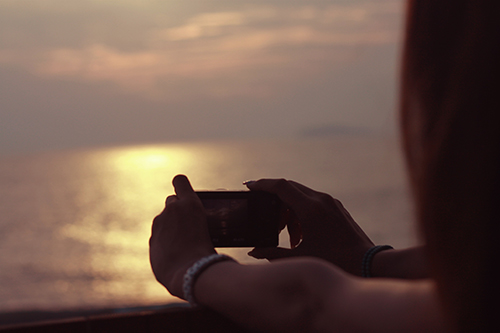 カメラで夕焼けの海を撮影する女の子