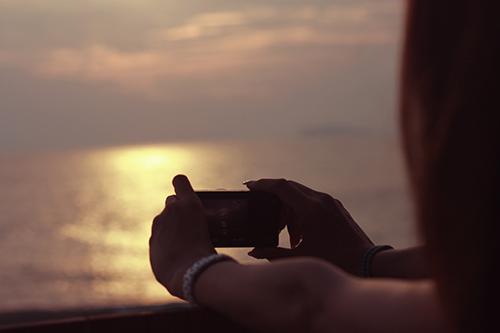 「カメラ」「夏の夕暮れ」「夕陽」「女性・女の子」「海」などがテーマのフリー写真画像