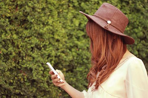 「iPhone」「スマートフォン」「女性・女の子」「巻き髪」「帽子」「秋」などがテーマのフリー写真画像
