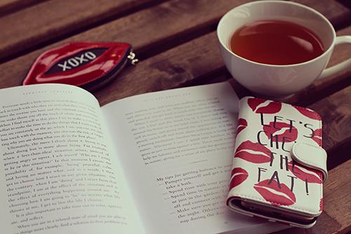 机に乗っている紅茶と本とスマートフォン