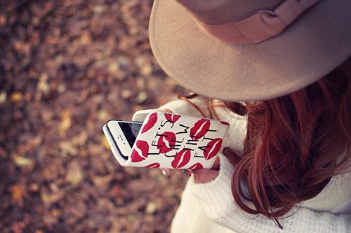 iPhoneをいじる秋服の女の子