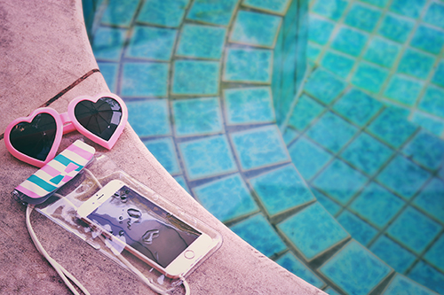 プールサイドに置かれたサングラスとApprilの可愛いスマホ防水ケース