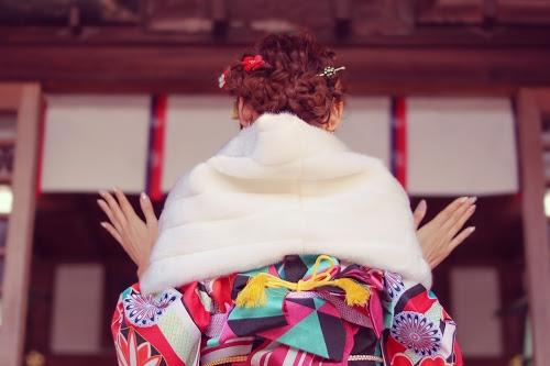 初詣で二礼二拍手一礼している着物の女の子