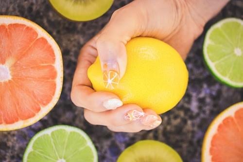 色々なフルーツたちの中からレモンを選び、ぐっと握る女の子の手