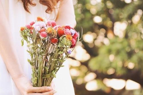 フリー写真素材:後ろ手に花束を持っている女の子