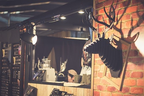 レンガ調の壁×鹿のオブジェがオシャレなカフェの内装