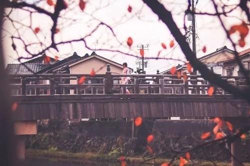 着物の女の子が橋を渡っている秋の金沢の風景