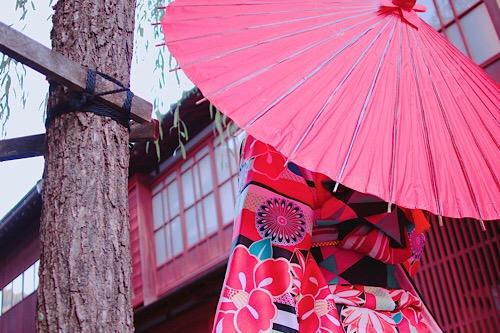 雨の金沢の風情ある茶屋街を歩く着物の女の子