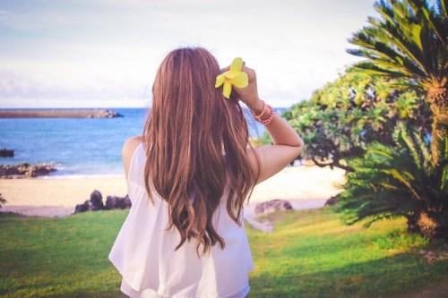 南国の海辺で黄色い花をこちらに差し出す女の子