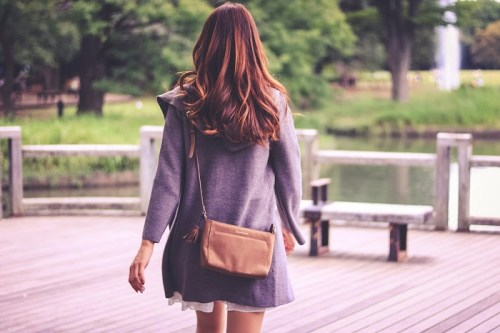 公園をてくてく歩いていく秋服をまとった女の子