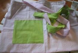"""Et forklæde til en lille pige. Her ses """"bagsiden"""" i lyserød med æblegrøn lomme."""