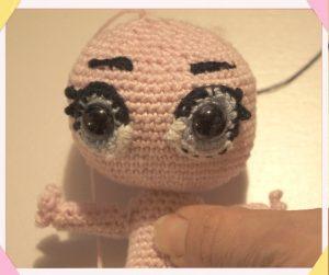 Occhi piccola bambola uncinetto lavorati con chiodini e contorno uncinetto