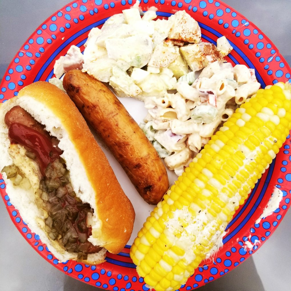 Coleman Naturals hotdog and sausage, potato salad, macaroni salad, and corn on the cob