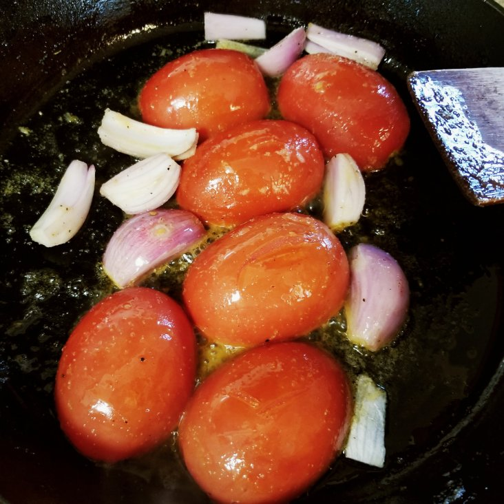 Using a cast iron pan to saute shallots and give tomatoes a nice char