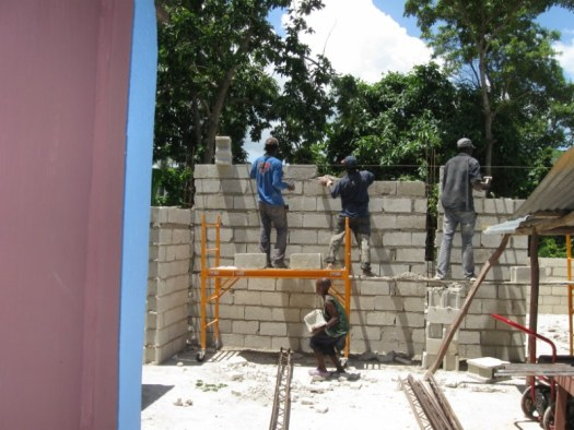 Men and boy hard at work on the mission house walls.