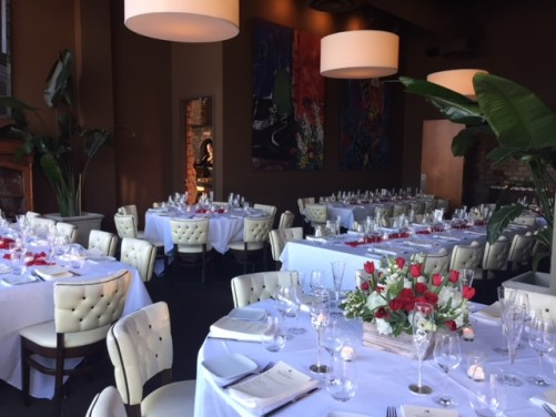 A picture of the private dining room at Cafe Lurcat, which is all set up for service with white linen tablecloths.