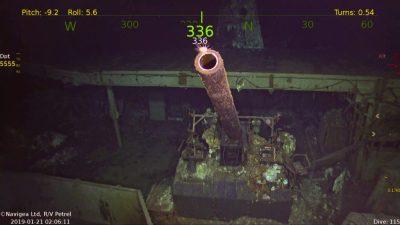 Imagem subaquática mostra um canhão de cor rosada e tamanho grande no porta-aviões, que está bastante deteriorado.