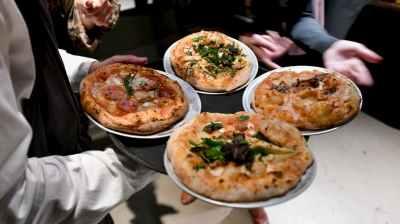 Homem carrega bandeja com quatro pizzas