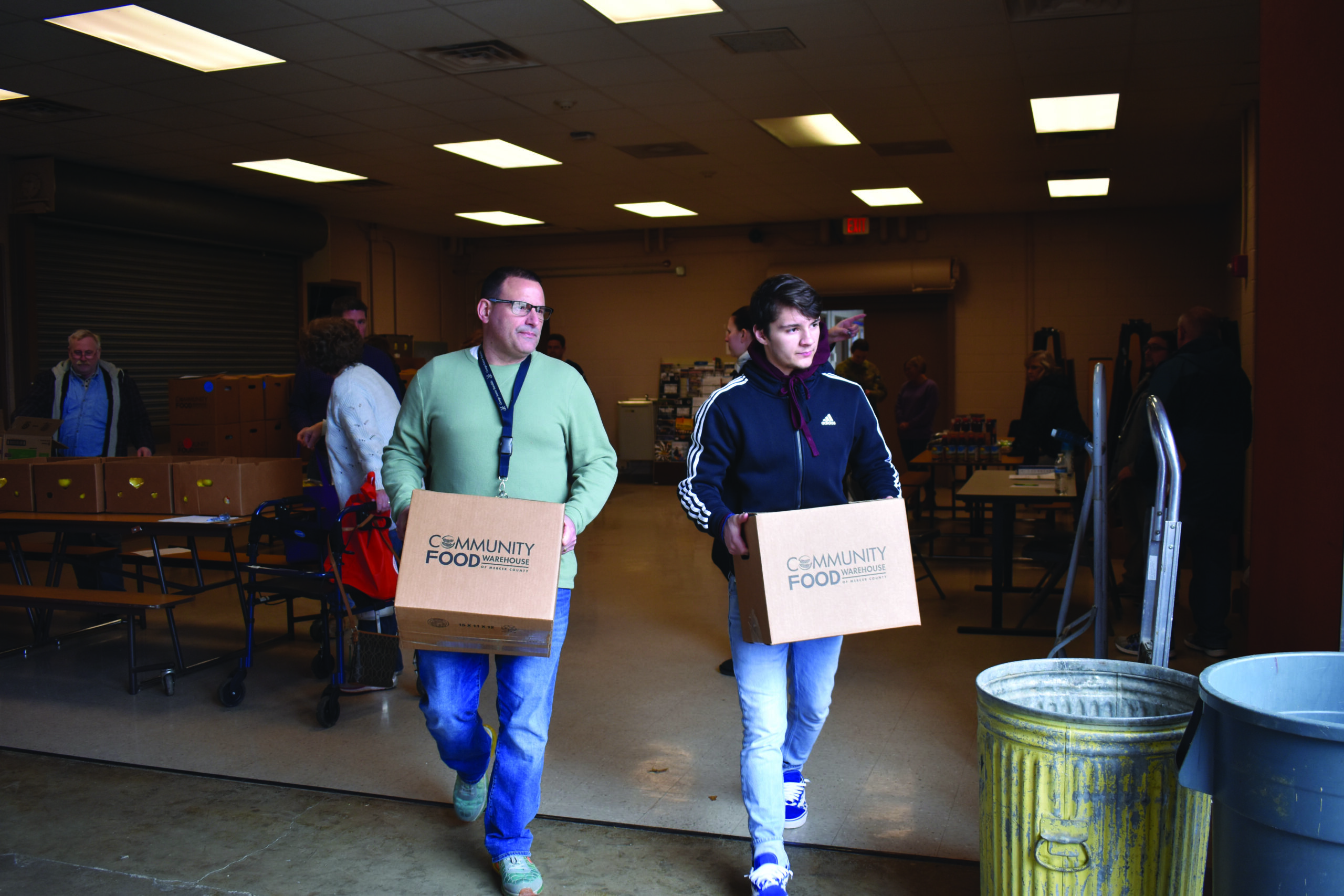 Staff and youth carrying boxes off food