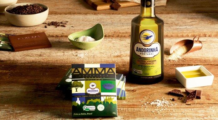 Uma mesa com os ingredientes do chocolate espalhados nela, no centro o chocolate com azeite da AMMA e ao lado uma garrafa de azeite Andorinha Extra Virgem.