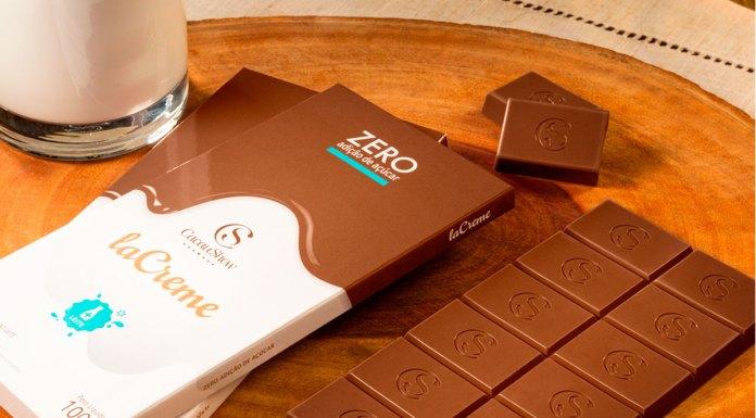 Tabletes de laCreme ao Leite Zero Adição de Açúcar da Cacau Show em uma mesa ao lado de um copo de leite.