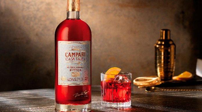 Uma garrafa de Campari Cask Tales, ao lado um copo com a bebida, com gelo e uma fatia de laranja. Ao fundo uma coqueteleira com fatias de laranjas.
