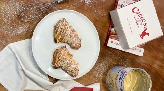 Foto de divulgação da linha de Dia das Mães da Carlo's Bakery com Leite Moça. Na foto, uma mesa com duas Lobster Tails Feito Com Moça, ao lado de um livro, uma caixa da loja, uma lata de Leite Moça e utensílios de confeitaria.