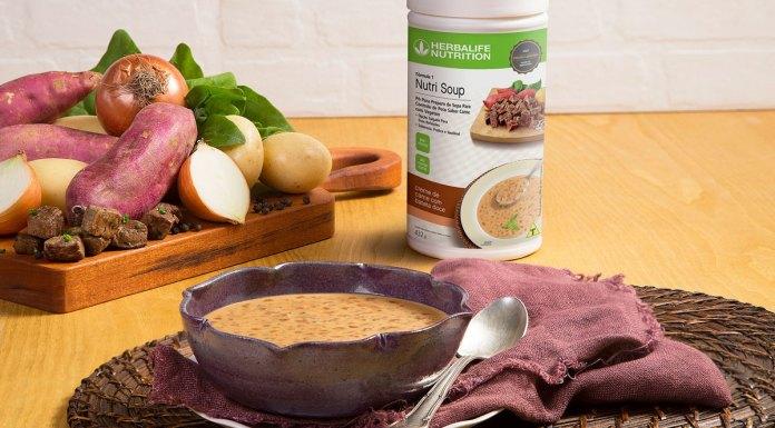 A foto apresenta uma mesa montada com uma tábua de batatas, um bowl com sopa, um jogo americano e uma colher, além de um pote de Nutri Soup Creme de Carne com Batata Doce