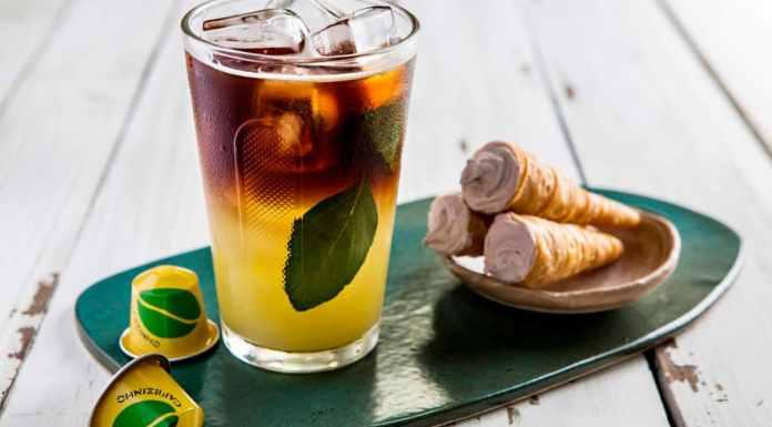 Foto de divulgação da Cafezinho do Brasil da Nespresso. A foto apresenta um copo com o café, com cápsulas e doce de cone ao lado.