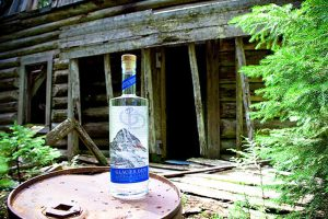 The finrest Distillerie near glacier park. Bottle of Glacier Dew in front of a cabin.