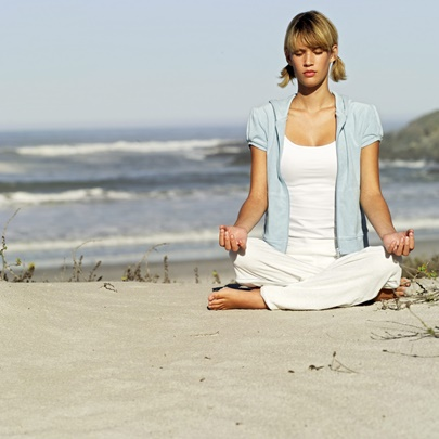 Young Woman Meditating at the Beach