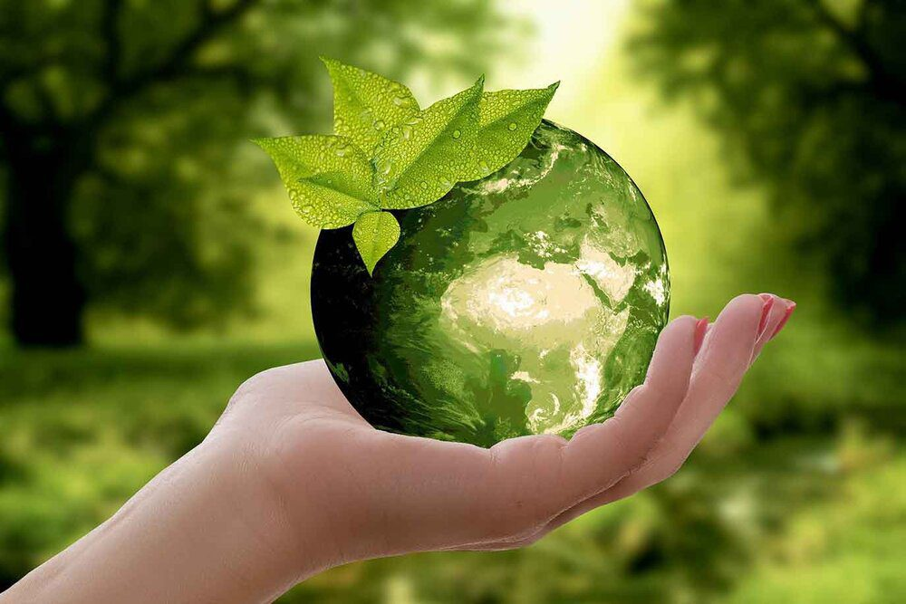 Save our planet - green living globe in hand
