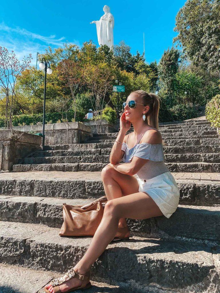 San Cristóbal Hill female travel blogger sat steps