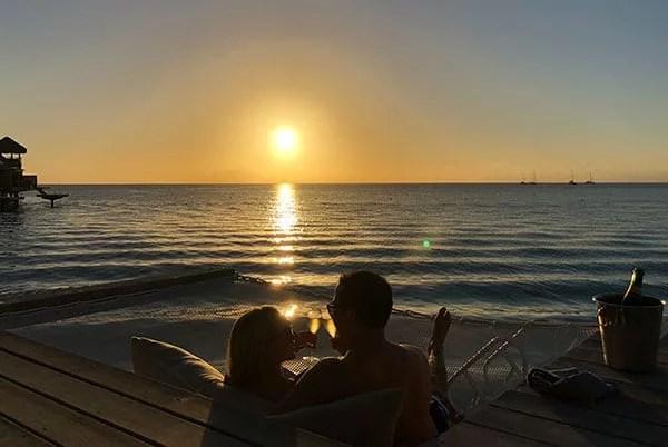 Romantic couple sunset overwater villa Conrad Bora Bora