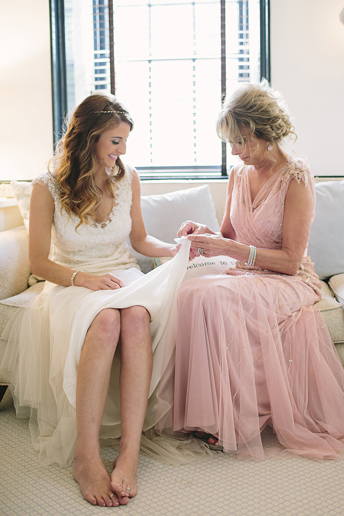 sewing a piece of her mother's and grandmother's gown onto the bride's | Brooke Courtney Photography | Glamour & Grace