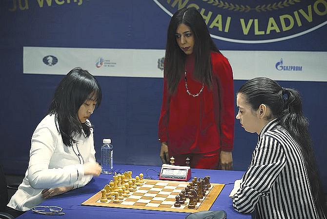 Die amtierende Schach-Weltmeisterin Ju Wenjun (links) schickt sich zum ersten Zug an, gespannt erwartet von ihrer Herausforderin Aleksandra Goryachkina. Im Hintergrund die iranische WM-Schiedsrichterin Shohreh Bayat.