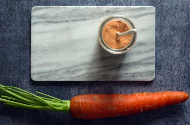 Karottenpulver im Glas neben einer knackigen, frischen Karotte