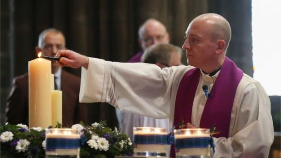Father David Wallace, chairman of Glasgow Churches Together, lights candles during the special service. Image copyright PA.