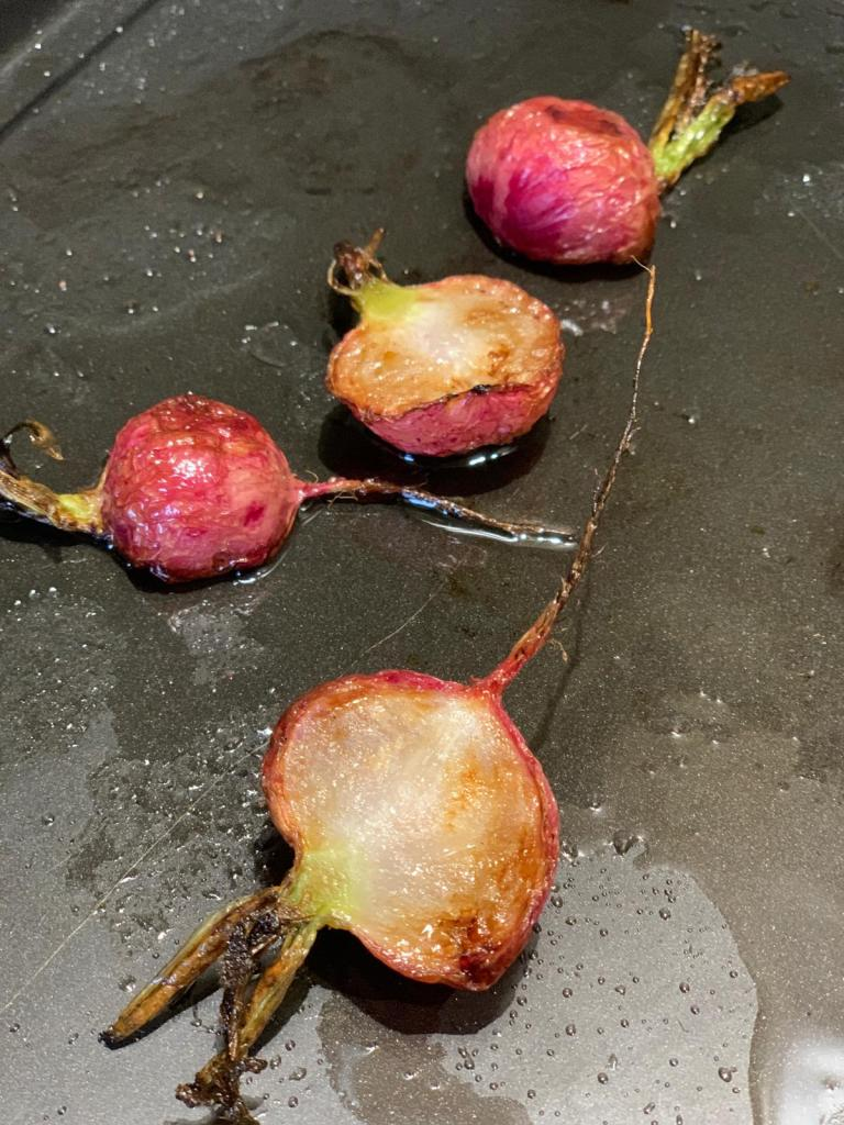 Radishes sliced whole in half and roasted on a black roasting tray
