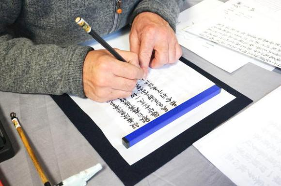 Zen group member copying the Heart Sutra during shakyo workshop